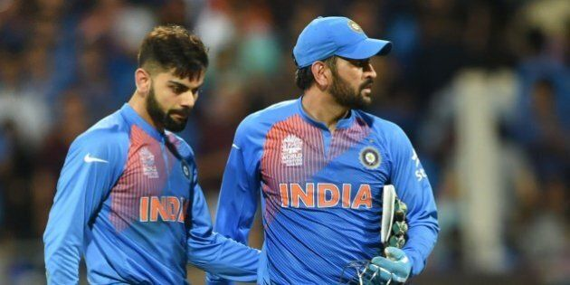 India's Virat Kohli(L)and captain Mahendra Singh Dhoni look on after defeat in the World T20 cricket...