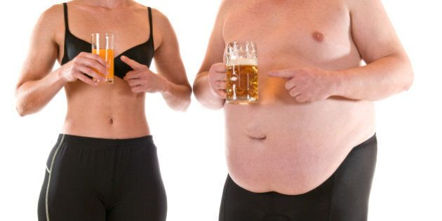 Young slim woman beneath a very fat man, both drinking orange juice and