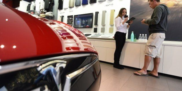 A salesrep (L) helps a customer pre-order the as yet unseen Tesla Model 3, in the Tesla store on the...