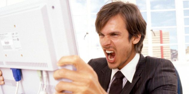 Businessman yelling at a computer