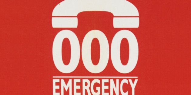 Sign indicating to call 000 in case of emergency, on the side of a phone booth in Sydney, Australia.