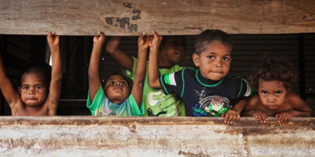 Aboriginal brothers and sisters playing in shed.