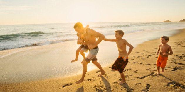 USA, California, Laguna Beach, Father playing football on beach with his three sons (6-7, 10-11,