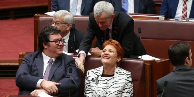 Anyone for a nut? Senator Malcolm Roberts shows a bag of cashews to Senator Pauline Hanson and George