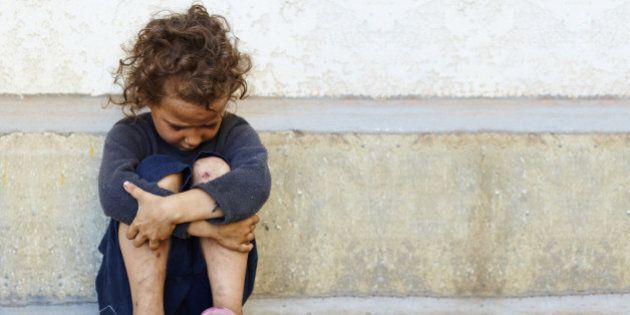 poor, sad little child girl sitting against the concrete