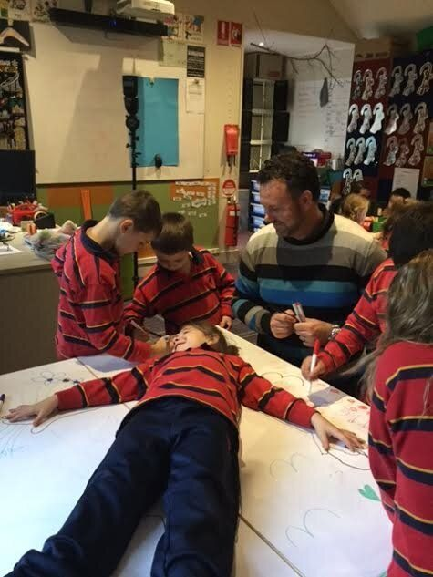 Teacher Jamie Shackleton supervising the kids tracing around one of their classmates...as you do.