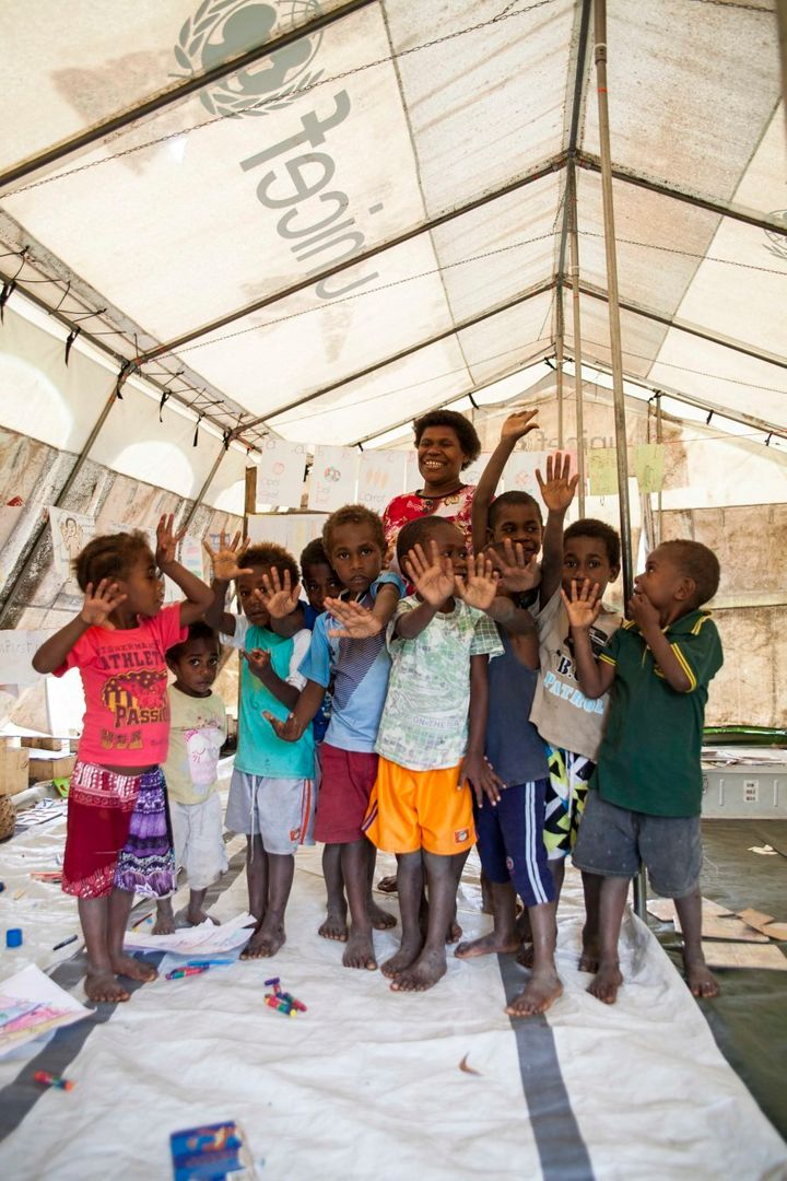 Kids from Loubukas Kindergarten sing and dance under the cover of a UNICEF tent after their schoolhouse was destroyed in Cyclone Pam. They have been given until 2018 to rebuild it, through their own funding and no government support. If this deadline isn't met they will be shut down.