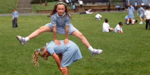 Children playing leapfrog in playground of primary school, Isle of Man UK. (Photo by: Photofusion/UIG...