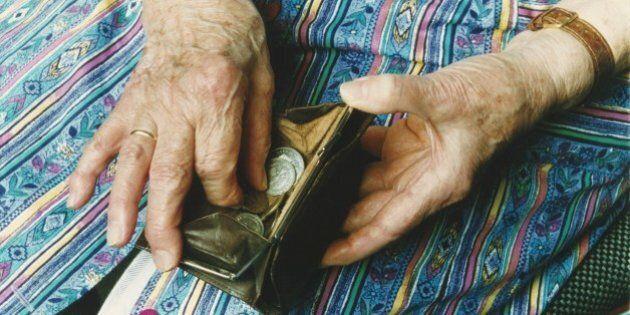 (GERMANY OUT) Eine alte Frau mit Kittelschürze hält ein geöffnetes Portemonnaie in der Hand und zählt...