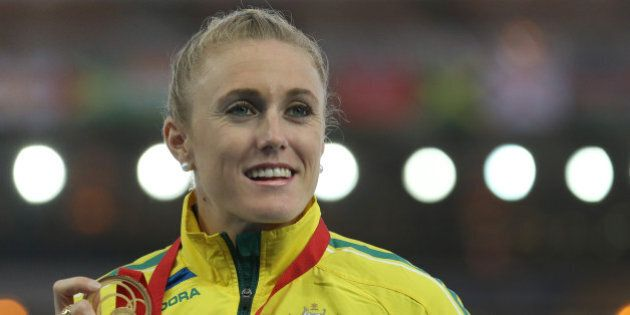 Sally Pearson of Australia winner of the women's 100 meter hurdle race poses for photographs on the podium...