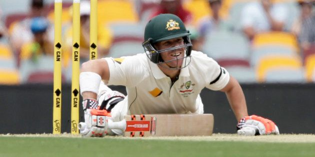 Australia's David Warner falls down after playing a shot during play on day one of the first cricket test between Australia and New Zealand in Brisbane, Australia, Thursday, Nov. 5, 2015. (AP Photo/Tertius Pickard)