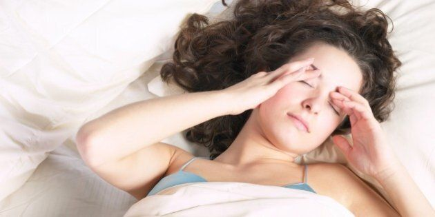 Woman in bed rubbing her eyes