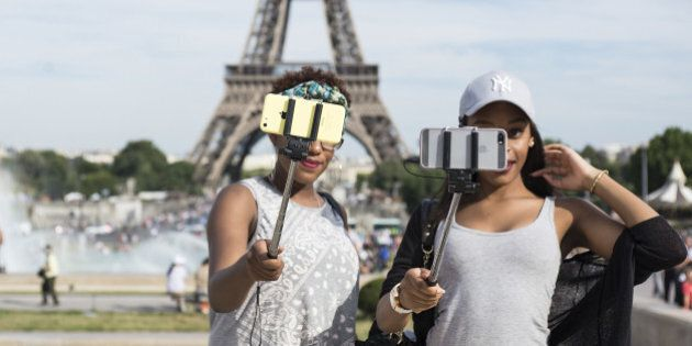PARIS, FRANCE - AUGUST 06: Tourists take a selfie using a selfie stick in front of the Eiffel Tower on...