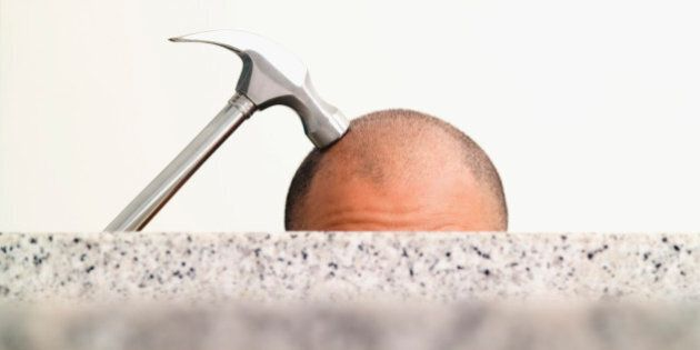 Hammer on top of man's shaved head, close-up