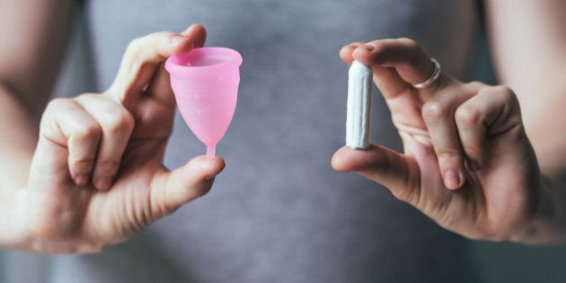 Young woman hands holding different types of feminine hygiene products - menstrual cup and