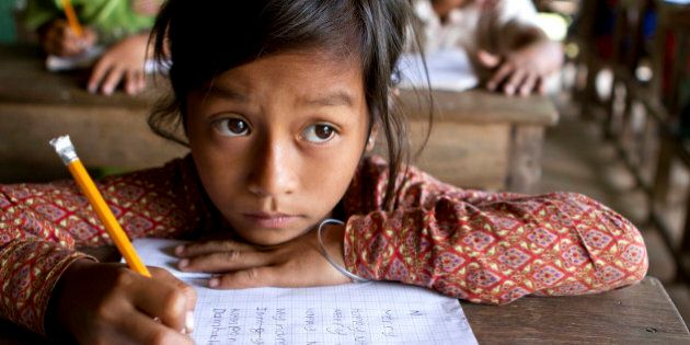 A young Asian girl studies hard her English writing skills (look at what she's writing