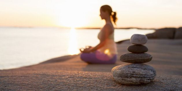 Side view of woman sitting in lotus position on lakeshore with focus on stack of