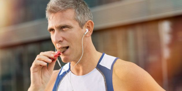 Portrait Of Fitness Mature Man Eating A Energy Bar Of