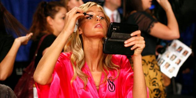 Model Erin Heatherton from the U.S. applies eye makeup backstage before the 2011 Victoria's Secret Fashion...