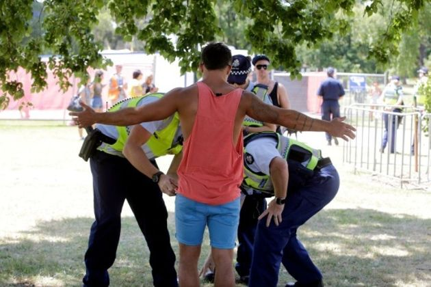 Police frisk a man for drugs at Melbourne's Stereosonic