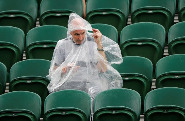 One die-hard fan sticks out the rain delay, equipped with rain