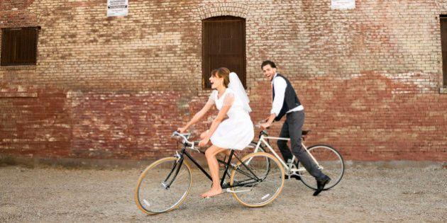 Bride and Groom riding their bikes, horizontal, brick