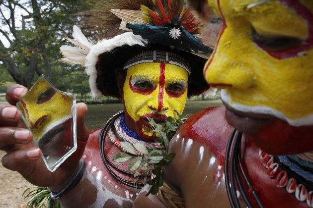 Tari wigman Nelson Yote (R) from Arou village checks his facial paint in a mirror fragment before performing...