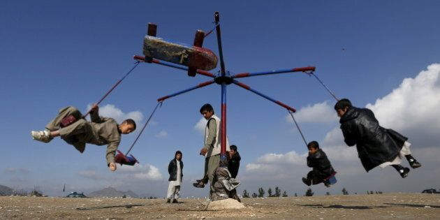 Afghan boys play on a merry-go-round during celebrations for the Afghan New Year, known as Newroz in...