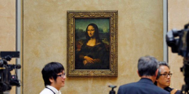 Members of the media are gathered next to Mona Lisa, during an event to unveil the new lighting of Leonardo...
