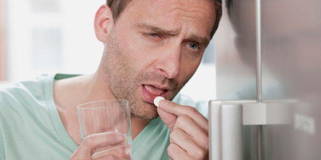Germany, Man taking medicine, close