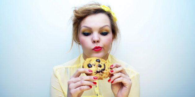 Young woman with ginger hair wearing a yellow blouse and colourful make-up staring at a smiling chocolate...