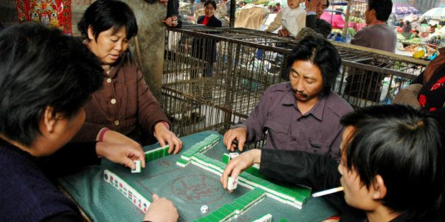 With little work to do without chickens, vendors play the popular Chinese game of mahjong next to empty...