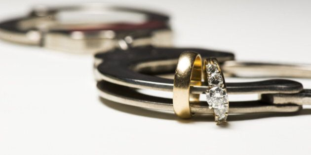 a close up of wedding rings and a handcuff showing people locked in