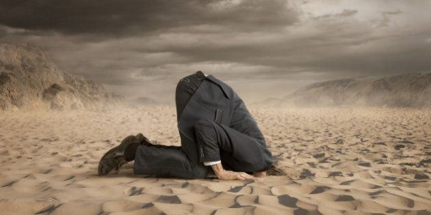 Young businessman hiding head in the sand