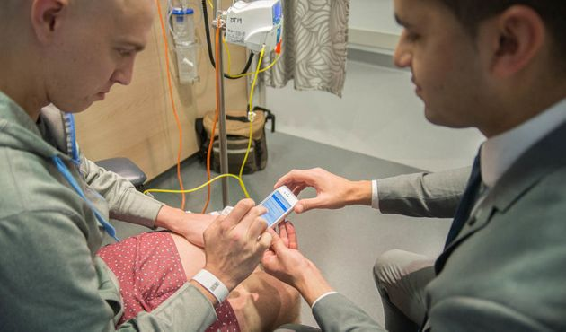 Pooviah shows Chris O'Brien Lifehouse patient Brendan Kennedy how the CancerAid app