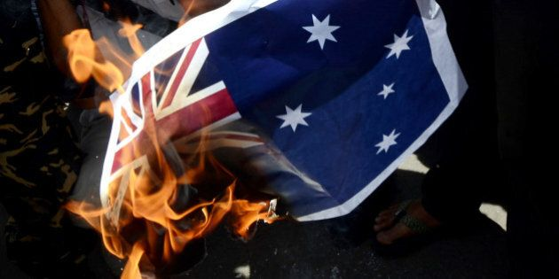 JAKARTA, INDONESIA - NOVEMBER 21: Indonesian activists burn the Australian Flag during a rally in front of the Australian embassy on November 21, 2013 in Jakarta, Indonesia. Approximately 200 demonstrators gathered at the Australian embassy in Jakarta in protest over reports the Australian government attempted to tap the phones of Indonesian President Susilo Bambang Yudhoyono in 2009. (Photo by Nurcholis Anhari Lubis / Getty Images)