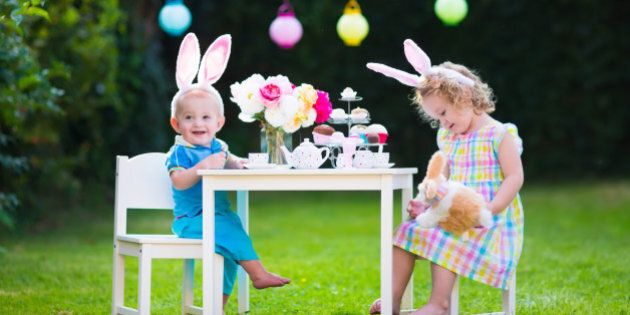 Little boy and girl play toy tea party outdoors. Children with bunny ears on Easter egg hunt. Kids playing...
