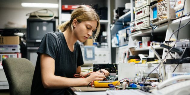 Young female engineer measuring voltage on a conductor board in her
