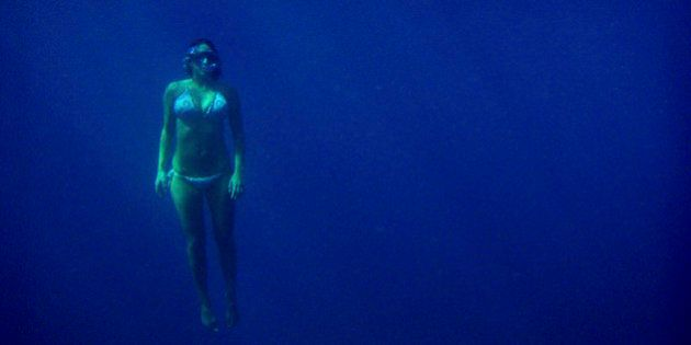 A female snorkeler rises from the depths of the ocean at Turtle Canyon in Hawaii.