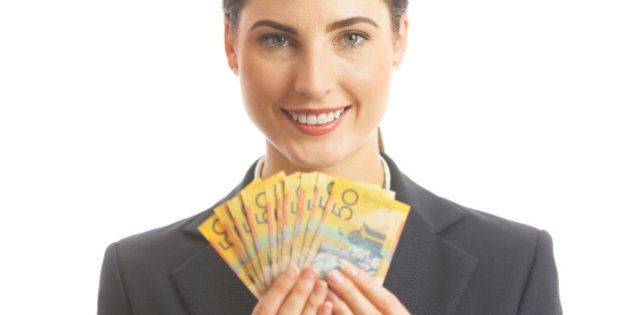 Close up of a happy business woman holding Australian cash. She is dressed in a corporate business suit,...