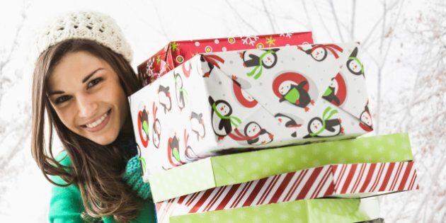Caucasian woman holding Christmas gifts in