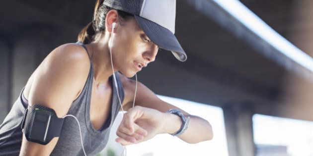 Woman looking at watch after exercising on city