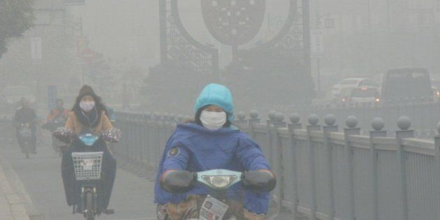 SUZHOU, CHINA - DECEMBER 07: (CHINA OUT) Cyclists wearing masks ride along a road in heavy smog on December...