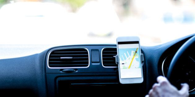 Taxi driver using GPS to follow the route. Travelling with GPS. Taxi (fictive) application on smart phone...