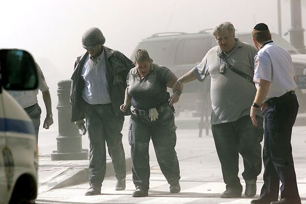 A paramedic and police officers walk away from the World Trade Center after one of the towers crumbled...