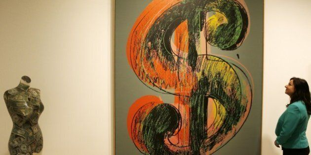 A woman looks at a piece of art entitled 'Dollar Sign, 1981,' an acrylic and silkscreen ink on canvas...