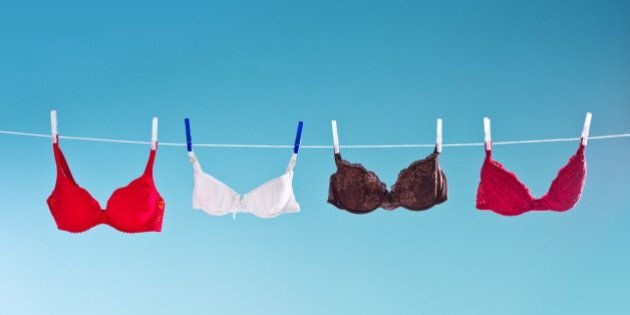 Laundry hangs out on a clothesline to dry. Colorful bras hanging against blue background. Summer