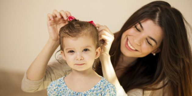 Pretty little Hispanic girl getting her hair done by her mom before they go out together
