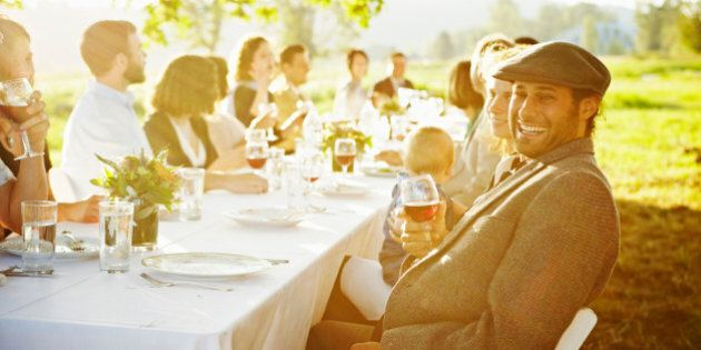 Man sitting at end of banquet table outside in field laughing holding glass of