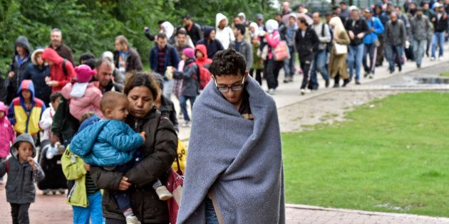 Migrants walk from the main station in Dortmund, Germany, to a hall where they get first attendance Sunday,...
